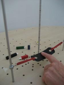 Fingerflexion/-extension mit der Fingerschlaufe. Die Alustange mit Maßeinteilung dient als Bewegungsziel bzw. zur Dokumentation des Therapieerfolges.